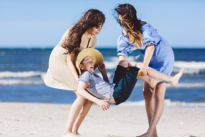 Two women carrying a boy in a straw hat on the beach.