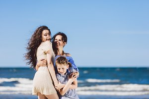 Mother, daughter and son hugging on the beach.