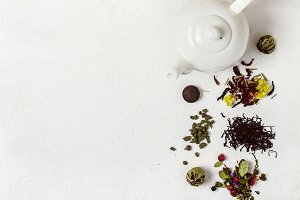 Tea concept. Selection of different varieties of tea and white teapot