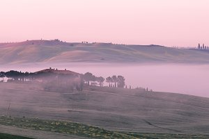 Morning fog view on farmhouse in