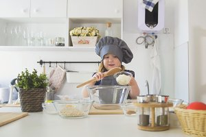Preschool girl baker sifts flour in a bowl for cooking biscuits