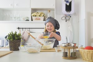 Little girl baker puts eags to the pastry dough for cooking biscuits