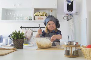 Girl baker mixes the mixture for cookies with a whisk