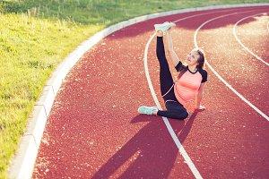 Sporty woman kneads her feet.