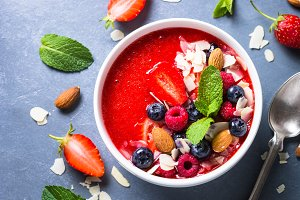 Smoothie bowl from strawberry with fresh berries and nuts.