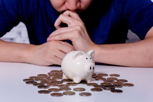 Young Asian man considering and thinking of saving money and investment and deposit with piggy bank and thai coins