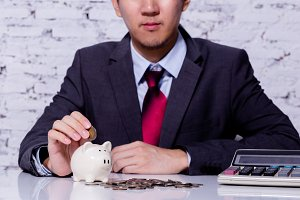 Businessman in formal suit putting and inserting coins in piggy bank with calculator nearby - business budgeting and saving for financial profit concept