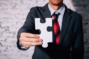 Business man giving the missing piece of jigsaw as offering a success, business solution in corporate partnership