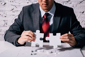 Hands of business man working on finishing last missing pieces of jigsaw on the white desk - critical thinking and problem solving business concept