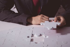 Young Businessman in suit holding the last missing piece of jigsaw and putting it to finish the critical thinking solution