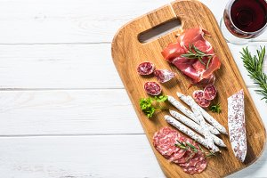 Antipasto delicatessen - meat, ham and wine on white.
