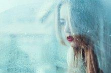 beautiful sad girl at a window