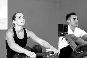 couple on rowing machine - workout