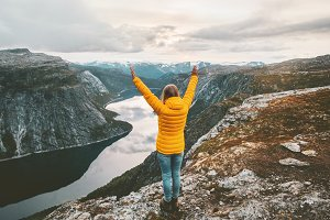Happy woman raised hands on mountain