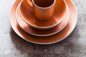 set of plates and a mug on a gray stone table. copy space. moder