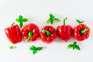 group of red ripe organic bell pepper and fresh basil leaves iso