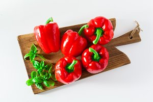 a group of red ripe organic peppers and fresh basil leaves on a