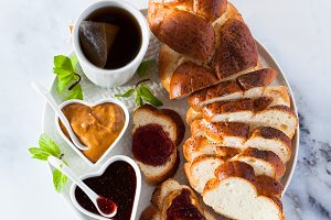 a morning breakfast with braided fresh bread, peanut butter, jam