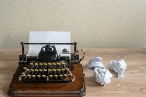 Old antique portable typewriter with screwed up paper on desk