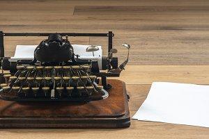 Old fashioned vintage portable typewriter on wooden desk