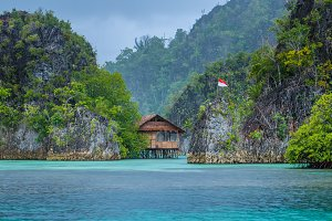 Bamboo Hut between some Rocks under Rain in Bay with Indonesian Flag, Pianemo Islands, Raja Ampat, West Papua, Indonesia