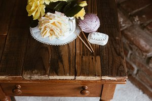 Roses and yarn on side table