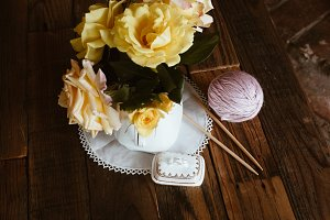 Roses and yarn with knitting needles