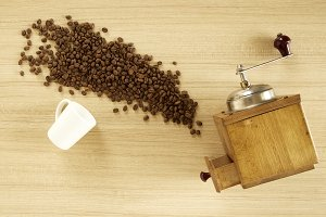Coffee grinder with coffee beans on wooden background