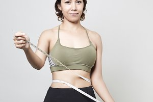 Fitness woman with measure tape on gray background