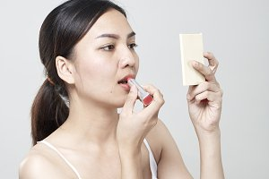 asian woman applying lipstick in mirror