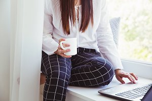 Woman with coffee cup and laptop