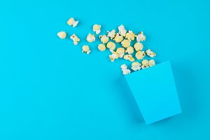 Box of popcorn spilled on blue background.
