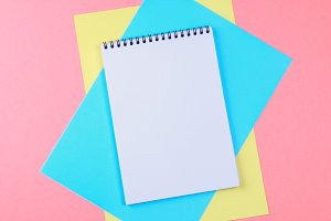 Top view flat lay picture with blank notepad page and different accessories on colored surface.