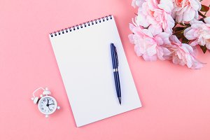 Empty notebook with blue pen on a pink pastel background. mock-up, frame, template.