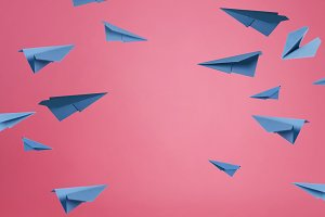 Lots of blue paper airplanes on pink