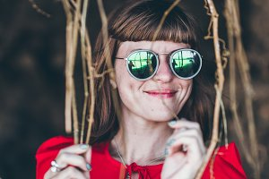 Close up shot of stylish young woman in sunglasses smiling. Beautiful female model with copy space. Bali island.