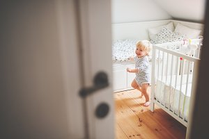Cute toddler boy running in a bedroom.