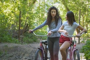 Two women on bicycles in the Park, summer day