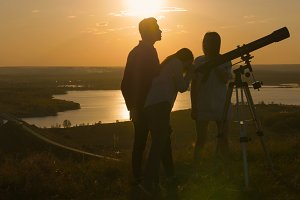 Young happy friends looks through per view telescope and having fun at summer sunset