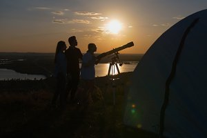 Young man showing friends beautiful view through telescope at summer sunset