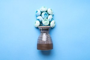 Vase with decorative flowers on blue background