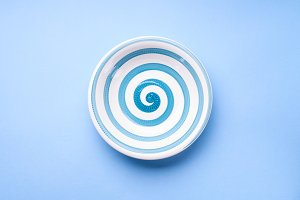Dish with hypnotizing spiral on pastel blue