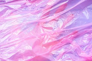 Hand under pink plastic bag film