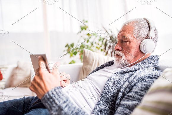 Senior Man With Tablet Relaxing At Home