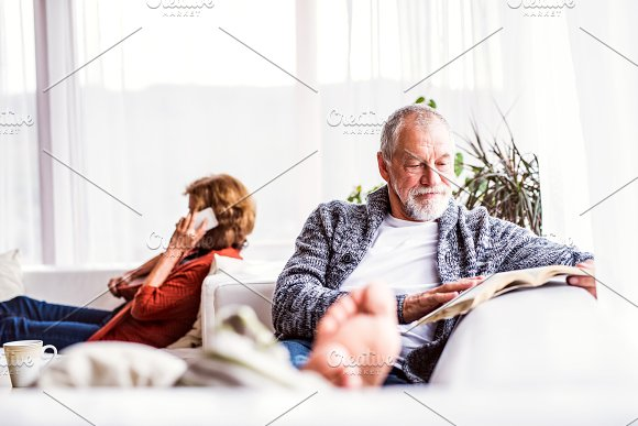 Senior Couple With Smartphone Relaxing At Home