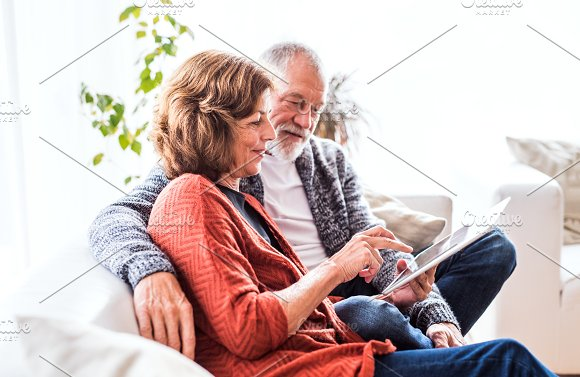 Senior Couple With Tablet Relaxing At Home