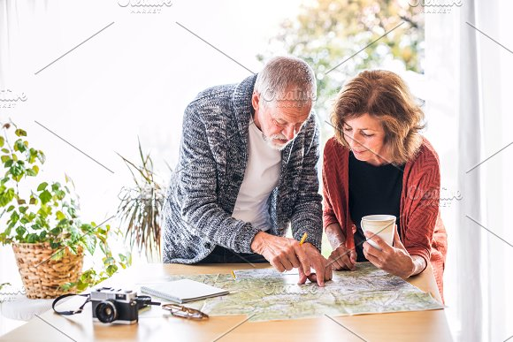 Senior Couple With Map At Home Making Plans
