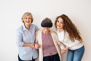 A teenage girl, mother and grandmother with VR goggles at home.