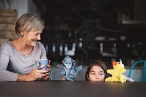 A small girl and grandmother with puppets at home.