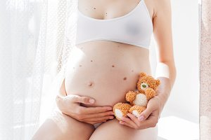 Pregnant woman with toy bear